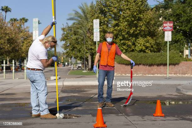 An employee and an undergraduate student collect a wastewater sample from a dorm sewage line to be tested for Covid-19 at the University of Arizona...