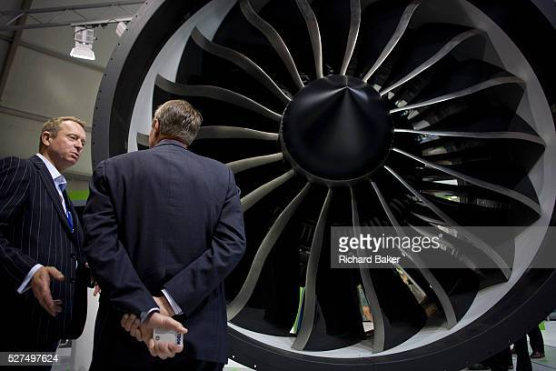 An employee and potential buyer discuss potential business deals at the General Electric jexhibition stand during the Farnborough Airshow The et...