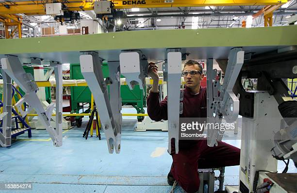 An employee applies undercoat paint to an Airbus SAS A380 aircraft wing a unit of European Aeronautic Defence Space Co at GKN Plc's Aerospace factory...