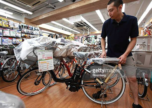 An employee arranges a batterypowered bicycle at a Cyclespot bicycle shop in Tokyo Japan on Friday July 31 2009 Domestic sales of hybrid bikes...