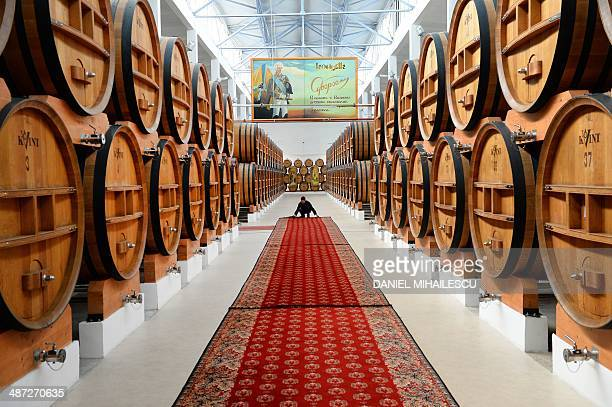 An employee arranges a carpet between brandy barrels at the wine- and brandy distillery KVINT in Tiraspol on April 17, 2014. Founded under the...