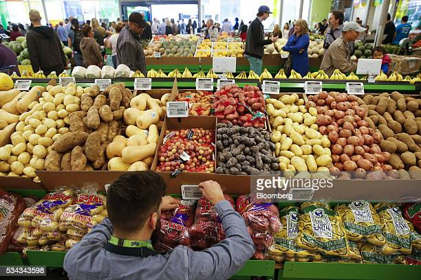 An employee arranges a digital price tag for vegetables on the opening day of the 365 by Whole Foods Market store in the Silver Lake neighborhood of...