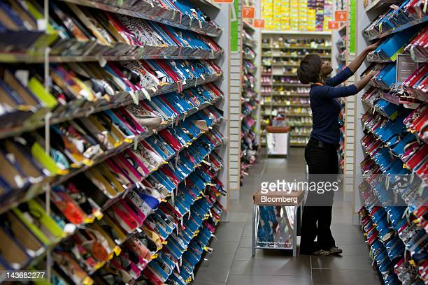 An employee arranges a display at a Payless ShoeSource Inc. Store in New York, U.S., on Wednesday, May 2, 2012. JPMorgan Chase & Co. And Wells Fargo...