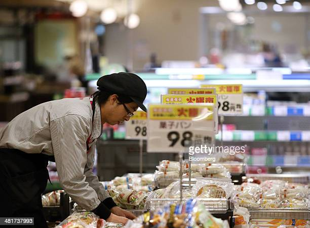 An employee arranges a display of breads at an Aeon Co supermarket in Chiba Japan on Monday March 31 2014 The country's consumption tax is being...