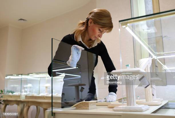 An employee arranges a display of diamond jewelry for sale inside a luxury jewelry store operated by Kristall Production Corp in Moscow Russia on...