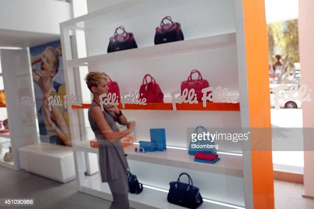 An employee arranges a display of ladies handbags inside ai Follie SA store in the Glyfada district of Athens Greece on Monday June 23 2014 Dimitrios...