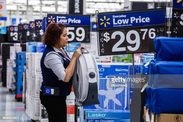 An employee arranges a fan on display for sale at a Walmart Inc store in Secaucus New Jersey US on Wednesday May 16 2018 Walmart is scheduled to...