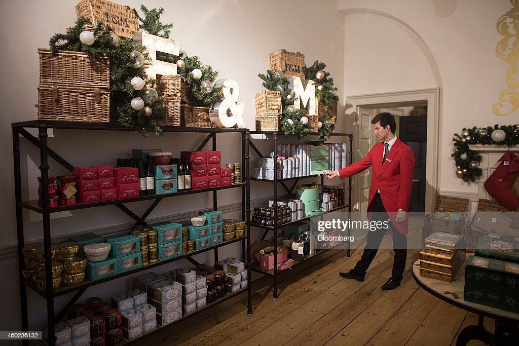 An employee arranges a festive shelf display inside a pop-up store, operated by Fortnum & Mason Plc, during a seasonal Christmas event at Somerset House in London, U.K., on Tuesday, Dec. 9, 2014. The British will be the biggest spenders in Europe on Christmas gifts this year, according to a study commissioned by Dutch bank ING Groep NV. Photographer: Simon Dawson/Bloomberg via Getty Images