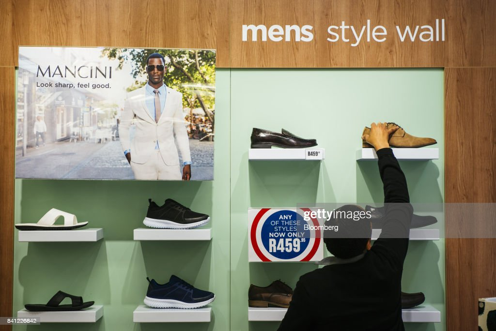 An employee arranges a shoe display on the men's style wall inside a Shoe City store, operated by Steinhoff International Holdings NV, in Pretoria, South Africa, on Thursday, Aug. 31, 2017. Steinhoffsaid like-for-like sales rose 8 percent as the South African furniture and clothing retailer achieved gains in its core European and African markets. Photographer: Waldo Swiegers/Bloomberg via Getty Images