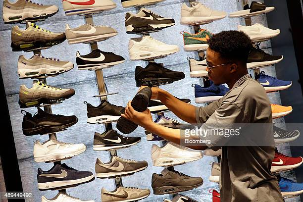 An employee arranges a sneaker display inside an Office fashion footwear store operated by Office Retail Group Ltd in this arranged photograph in...