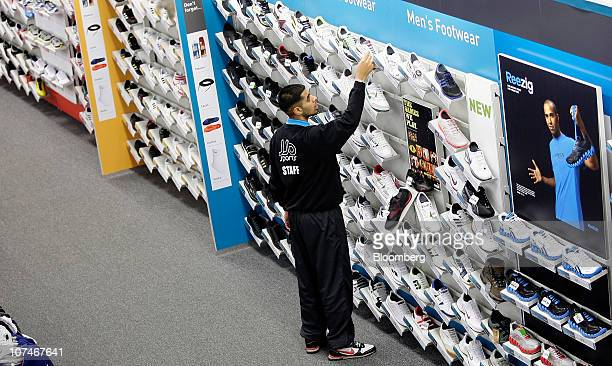 An employee arranges a sports shoes display at a JJB store operated by JJB Sports Plc in Slough UK on Thursday Dec 9 2010 While snow and freezing...