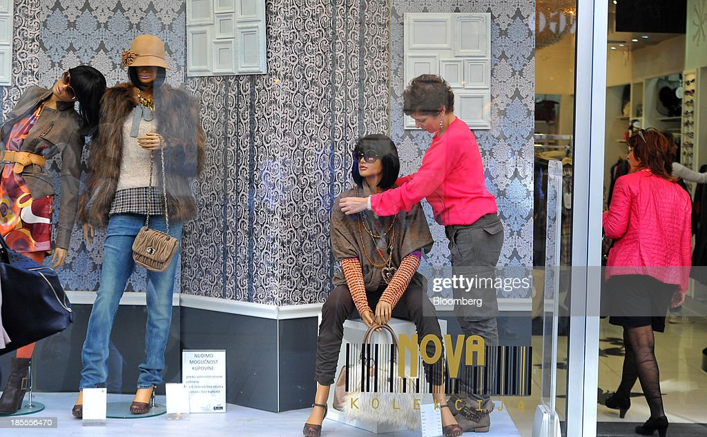 An employee arranges a window display at a women's retail fashion clothing store in Belgrade, Serbia, on Monday, Oct. 21, 2013. Serbia's government revealed a salvo of measures to bring the public finance deficit and debt back under control by 2017 after the head of the largest coalition party warned the country was on the brink of insolvency. Photographer: Oliver Bunic/Bloomberg via Getty Images
