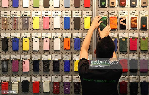 An employee arranges Apple iPhone cases at the at the DParts stand at the Internationale Funkausstellung 2012 consumer electronics trade fair on...