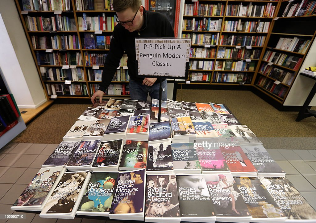An employee arranges books published by the Penguin publishing house, part of Pearson Plc, at a bookstore in London, U.K., on Friday, April 5, 2013. Bertelsmann SE's Random House won European Union approval to buy Pearson Plc's Penguin unit to create the largest book publisher in the U.K. and the U.S. Photographer: Chris Ratcliffe/Bloomberg via Getty Images