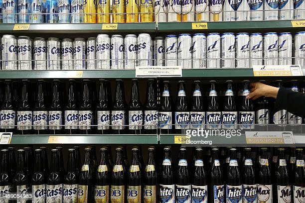 An employee arranges bottles of Hite Jinro Co. Hite beer at an E-Mart Co. Store, a subsidiary of Shinsegae Co., in Incheon, South Korea, on Saturday,...