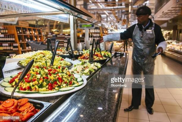 An employee arranges bowls of fresh vegetables at the self service salad bar inside a Pick n Pay Stores Ltd supermarket in Johannesburg South Africa...