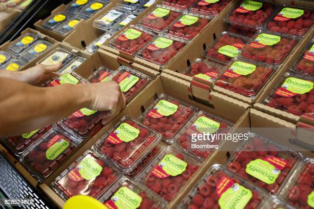 An employee arranges boxes of Driscoll's raspberries during the grand opening of a Whole Foods Market 365 location in Santa Monica California US on...