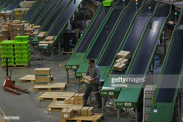 An employee arranges boxes of pharmaceutical products on pallets for distribution to customers at the Cofares SA logistical plant in Guadalajara...