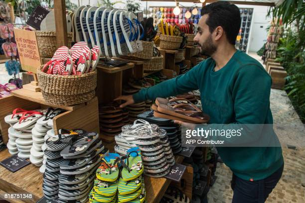 An employee arranges Brazilian Havaianas flipflops at a stand in Sao Paulo Brazil on July 18 2017 The Havaianas ambassadors of Brazil in the world...