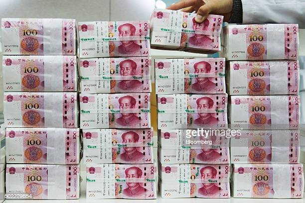 An employee arranges bundles of Chinese onehundred yuan banknotes at the Counterfeit Notes Response Center of KEB Hana Bank in Seoul South Korea on...