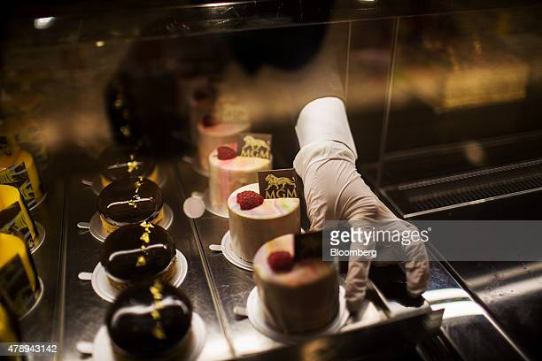 An employee arranges cakes inside a display at the Pastry Bar in the MGM Macau casino resort operated by MGM China Holdings Ltd in Macau China on...