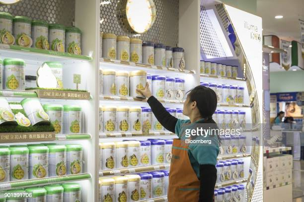 An employee arranges cans of Illuma infant formula produced by Nestle SA on a shelf at a Shanghai Aiyingshi Co Babemax store in Shanghai China on...