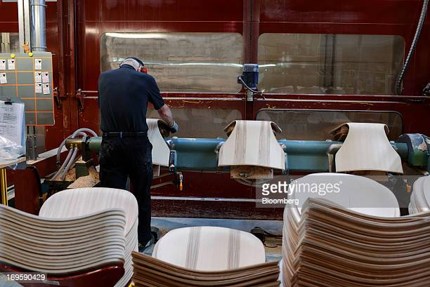 An employee arranges chair seats on a machine for sanding during manufacture at the Fritz Hansen A/S furniture company's assembly plant in Lynge...