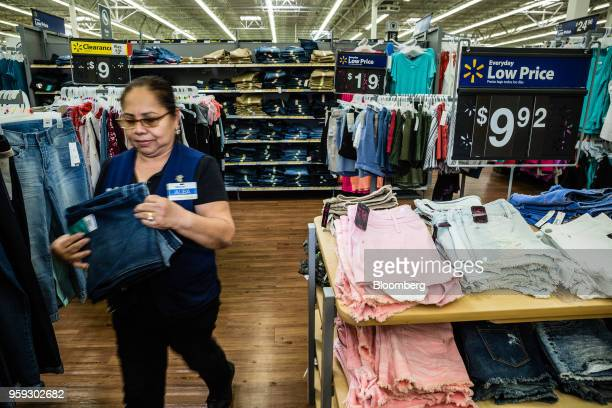 An employee arranges clothing at a Walmart Inc store in Secaucus New Jersey US on Wednesday May 16 2018 Walmart is scheduled to release earnings...