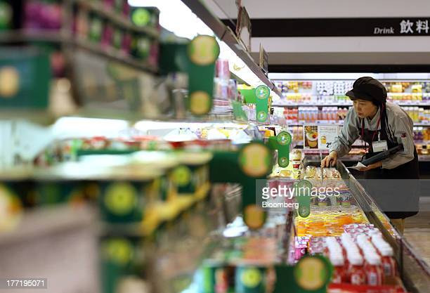 An employee arranges dairy products at an Aeon Co supermarket during a sale jointly held with Daiei Inc at an Aeon supermarket in Tokyo Japan on...