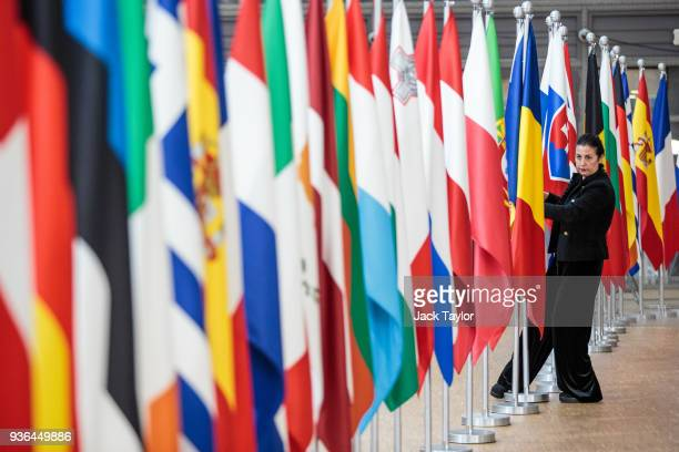An employee arranges European Flags at the Council of the European Union on the first day of the European Council leaders' summit on March 22 2018 in...