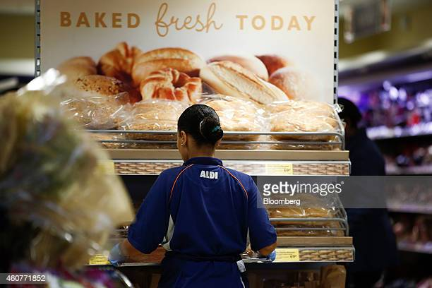 An employee arranges freshly baked bread on a display at an Aldi Stores Ltd supermarket in the Kilburn district of London UK on Monday Dec 22 2014...