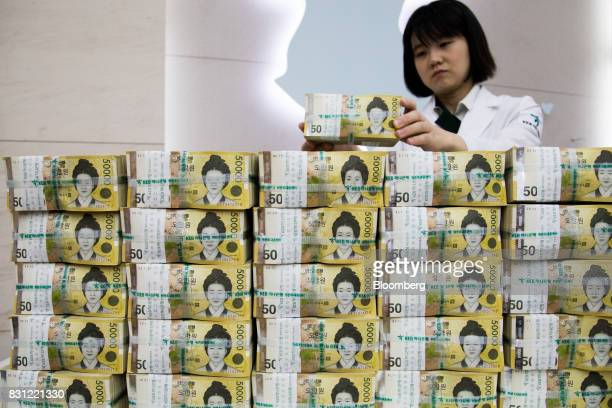 An employee arranges genuine bundles of South Korean 50000 won banknotes for a photograph at the Counterfeit Notes Response Center of KEB Hana Bank...
