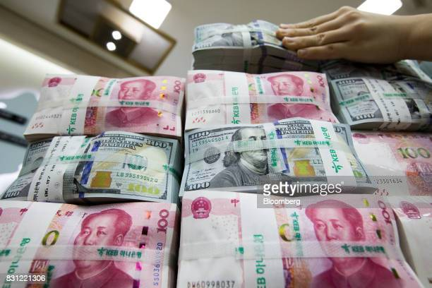 An employee arranges genuine bundles of US onehundred dollar banknotes and Chinese onehundred yuan in an arranged photograph at the Counterfeit Notes...