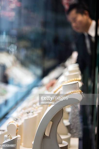 An employee arranges gold jewelry in the window display of a Chow Tai Fook Jewellery Group Ltd store in the shopping district of Tsim Sha Tsui in...