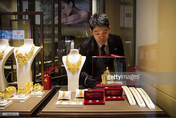 An employee arranges gold rooster figurines in the window of a Chow Tai Fook Jewellery Group Ltd store in the Central district of Hong Kong China on...