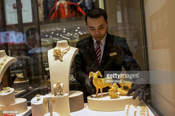 An employee arranges gold sheep figurines in the window of a Chow Tai Fook Jewellery Group Ltd jewelry store in the Central district of Hong Kong...