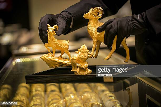 An employee arranges gold sheep figurines inside a Chow Tai Fook Jewellery Group Ltd jewelry store in the Central district of Hong Kong China on...