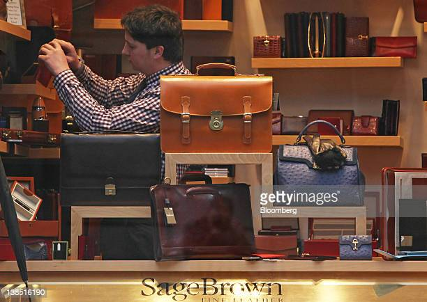 An employee arranges goods for sale at the Sage Brown leather goods store at the Royal Exchange luxury shopping and dining arcade in London UK on...