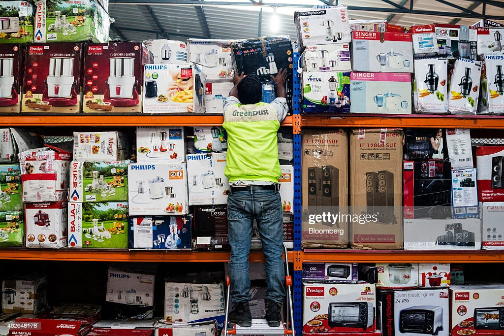 An employee arranges household products stored on shelves in the small appliances section at the refurbishment facility of GreenDust, a unit of Reverse Logistics Co., in New Delhi, India, on Friday, Jan. 16, 2015. Reverse Logistics, an Indian retailer of refurbished goods, is a factory outlet store in India selling goods through its GreenDust brand franchise stores and website. Photographer: Prashanth Vishwanathan/Bloomberg via Getty Images