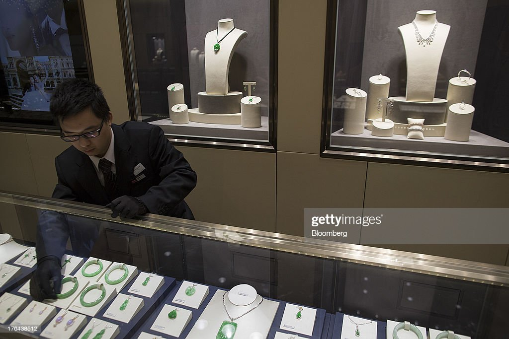 An employee arranges jade jewelry in a display cabinet at a Chow Tai Fook Jewellery Group Ltd. retail store in the Central district of Hong Kong, China, on Tuesday, July 23, 2013. The value of the precious gem is surging with Chinas wealthy snapping up jade necklaces, rings and bracelets as long-term investments. Photographer: Jerome Favre/Bloomberg via Getty Images