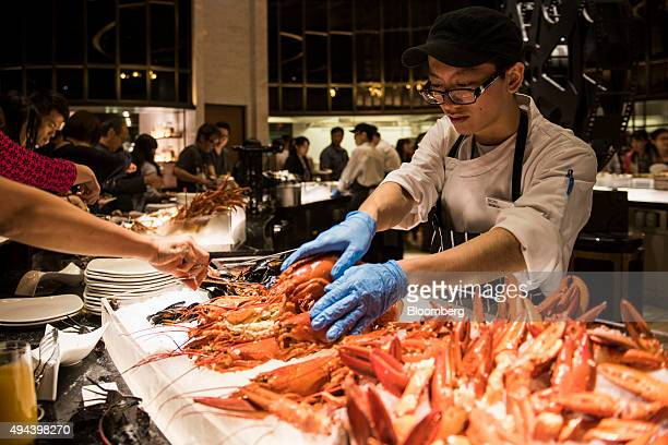 An employee arranges lobsters at a buffet in the Spotlight restaurant at the Studio City casino resort developed by Melco Crown Entertainment Ltd...