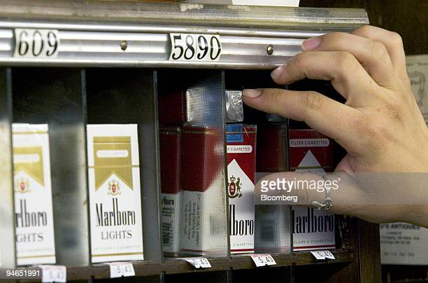 An employee arranges Marlboro cigarettes at Leavitt and Peirce Tobacco in Cambridge Massachusetts Tuesday July 25 2006 Altria Group Inc the world's...