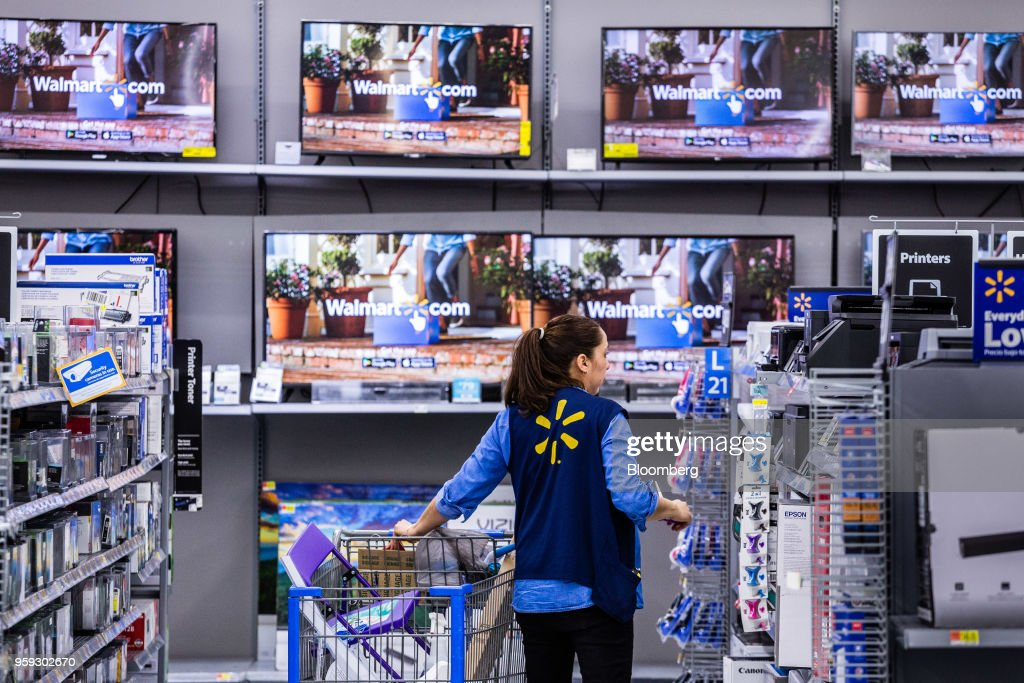 An employee arranges merchandise at a Walmart Inc. store in Secaucus, New Jersey, U.S., on Wednesday, May 16, 2018. Walmart is scheduled to release earnings figures on May 17. Photographer: Timothy Fadek/Bloomberg via Getty Images