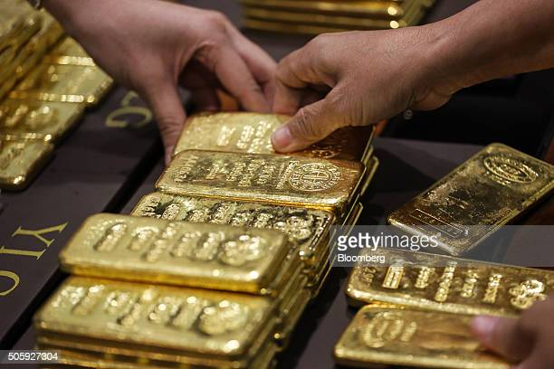 An employee arranges one kilogram gold bars for a photograph at the YLG Bullion International Co headquarters in Bangkok Thailand on Wednesday Jan 13...