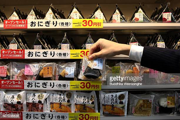 An employee arranges Onigiri, rice balls at a newly designed train-shaped convenience store named Lawson + Friends on its opening day at the Itayado...
