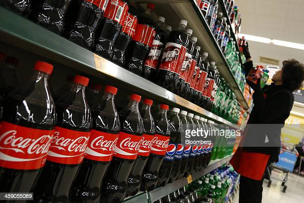 An employee arranges packages of CocaCola Co soda drinks at an EMart Co store a subsidiary of Shinsegae Co in Incheon South Korea on Saturday Dec 21...