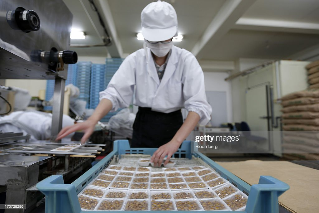 An employee arranges polystyrene trays of steamed soybeans, sprayed with the Bacillus subtilis natto bacterium for fermentation, in a crate at the Matsushita Shoten Y.K. production facility in Kawasaki, Kanagawa Prefecture, Japan, on Friday, June 7, 2013. From Japan's natto makers and operators of neighborhood baths to its largest refiner and utilities, the weaker yen offers domestically focused industries nothing to offset higher import prices. Photographer: Kiyoshi Ota/Bloomberg via Getty Images