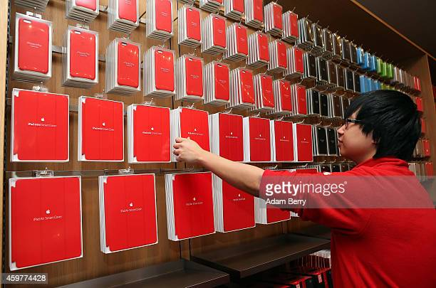 An employee arranges red iPad cases at the Apple Store on December 1 2014 in Berlin Germany On World AIDS Day December 1 Apple is donating a portion...