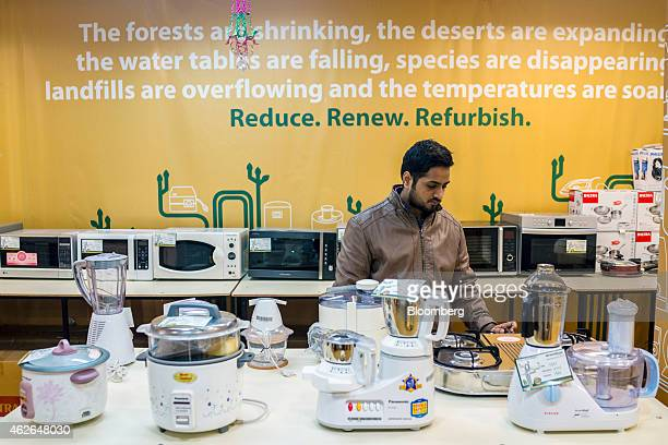 An employee arranges refurbished kitchen goods on display inside a store of GreenDust a unit of Reverse Logistics Co in the Neb Serai area of New...