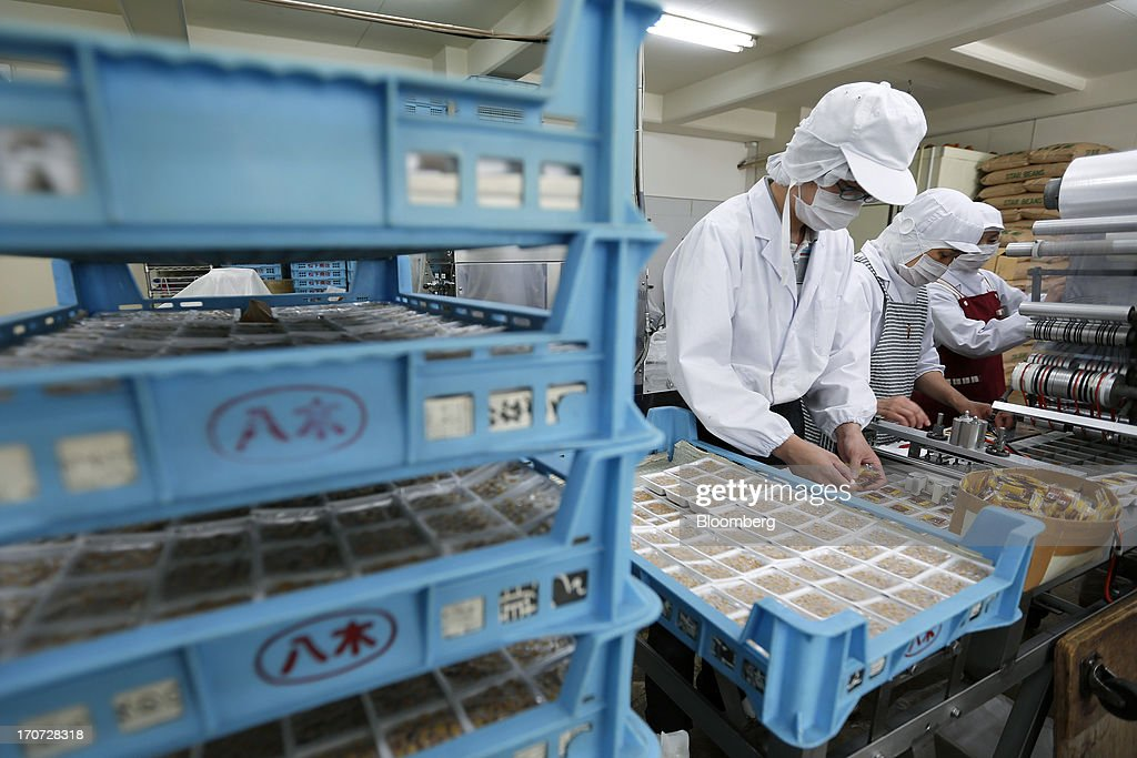 An employee arranges sachets of seasoning sauce and mustard onto polystyrene trays of fermented soybeans, known as natto, at the Matsushita Shoten Y.K. production facility in Kawasaki, Kanagawa Prefecture, Japan, on Friday, June 7, 2013. From Japan's natto makers and operators of neighborhood baths to its largest refiner and utilities, the weaker yen offers domestically focused industries nothing to offset higher import prices. Photographer: Kiyoshi Ota/Bloomberg via Getty Images